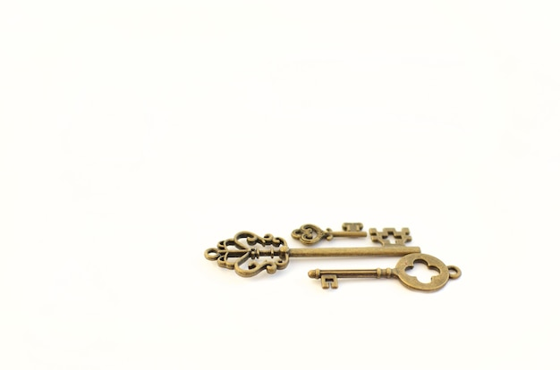 Декоративные ключи разных размеров, стилизованные под старину на белом фоне. сформируйте центральную часть. три ключа