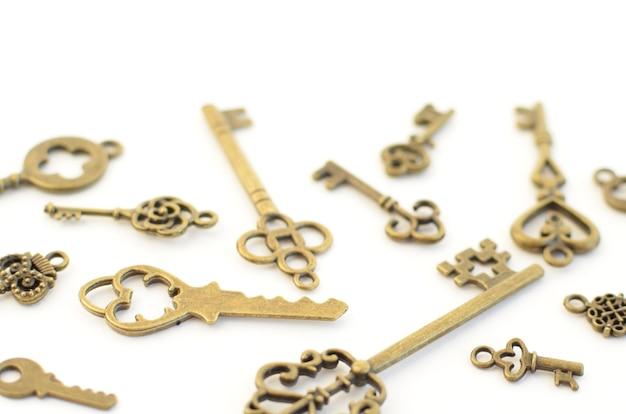 Декоративные ключи разных размеров, стилизованные под старину на белом фоне. сформируйте центральную часть.