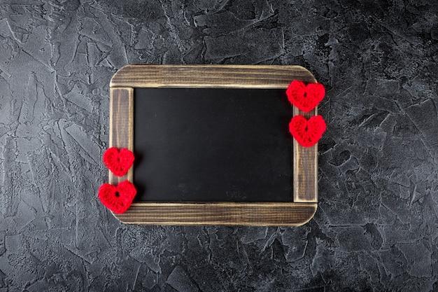 装飾的なニットのかぎ針編みのハートと黒板。バレンタイン・デー。フラットレイ。上面図。