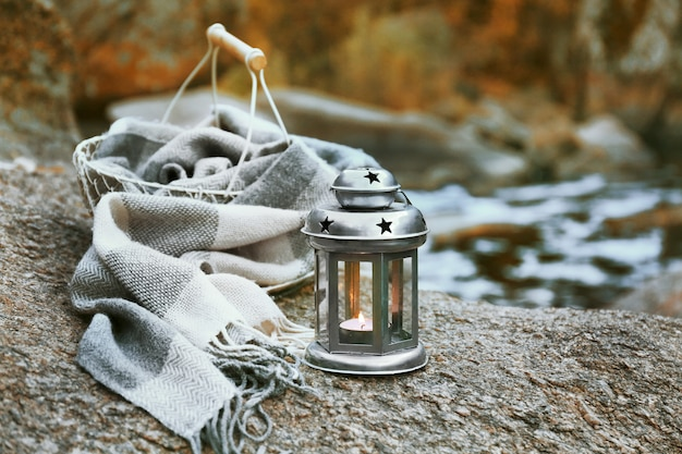Decorative lamp, basket and plaid on rock in the forest