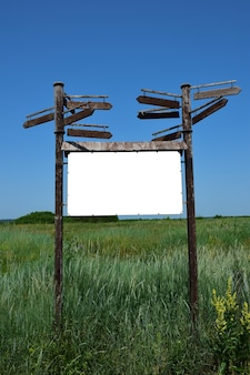 Decorative large signpost of three horizontal boards with blank space for inscriptions on each of them against a background of green grass