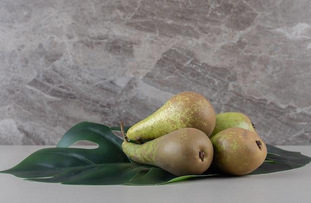 Foglia decorativa sotto un mazzetto di pere su marmo