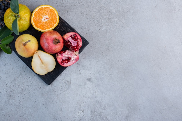 Декоративные листья с нарезанными и целыми грушами, гранатами и мандаринами на черной доске на мраморном фоне.