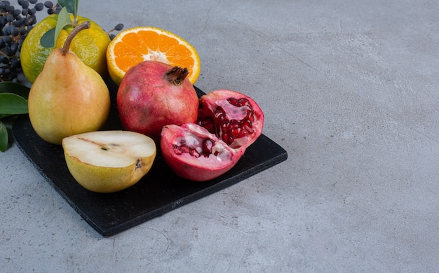Decorative leaves with sliced and whole pears, pomegranates and tangerines on a black board on marble background.
