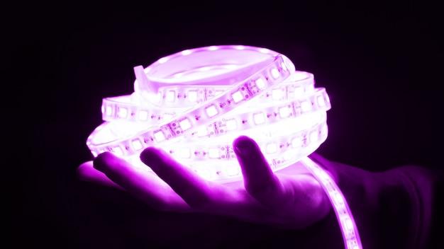 Декоративная светодиодная лента пурпурного цвета в руке.