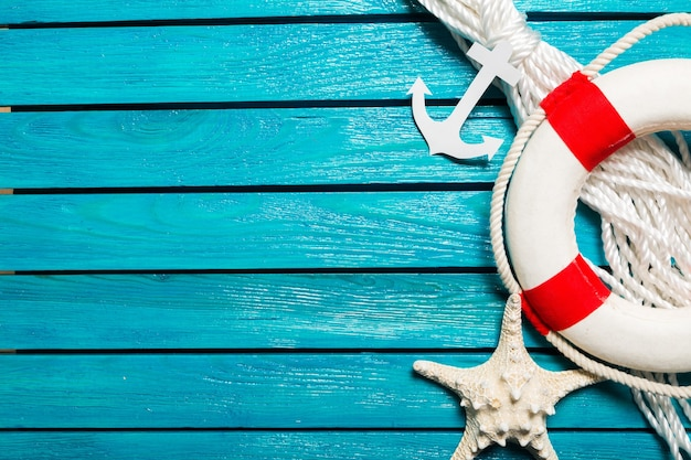 Decorative lifebuoy and anchor on blue wooden planks background