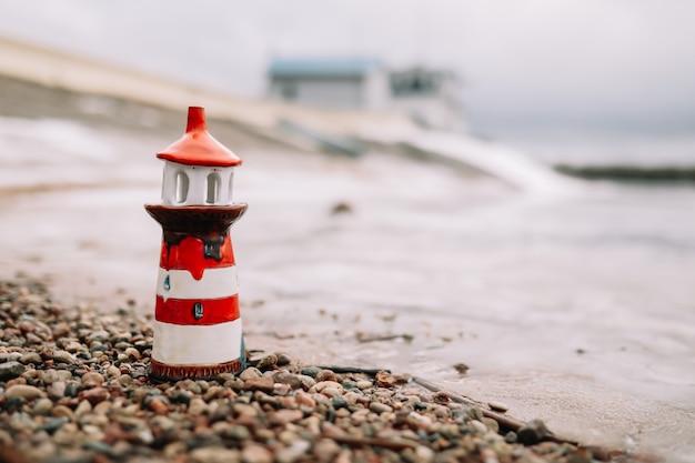 Декоративный маяк на море зимой. замерзшее море с маяком. морской образ жизни. зима, море, путешествия, приключения, праздники и концепция отпуска. путешествие в 2021 году