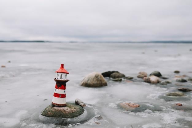 Декоративный маяк на море зимой. замерзшее море с маяком. зима, море, путешествия, приключения, праздники и концепция отпуска. путешествие в 2021 году