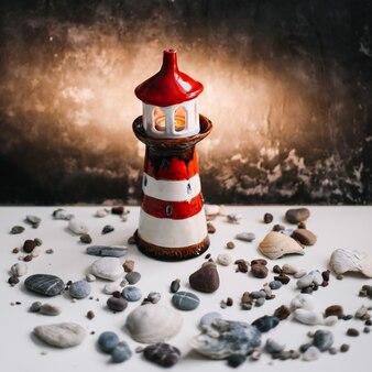 Декоративный маяк с морскими ракушками и камнями на темноте