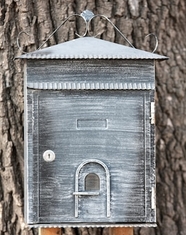 Decorative mailbox hanging on a tree.