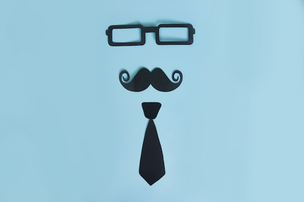 Decorative man mustache, black glasses and bow-tie on a light blue wood