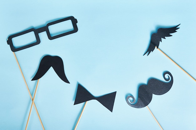 Decorative man mustache and black glasses on a light blue paper