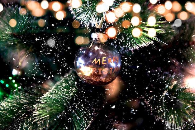 きらめくライトが付いている木の上の装飾的なメリークリスマスのおもちゃ。セレクティブフォーカス。お祭りの背景。