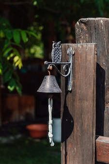 Decorative metal bell with an owl at the entrance to the house vertical