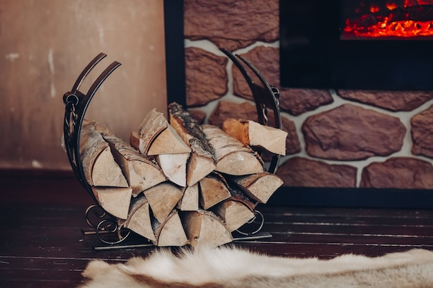 Decorative metallic holder with heap of wooden logs next to stony fireplace with burning logs.