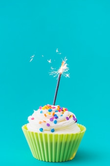 Decorative muffin with illuminated sparkler on turquoise background