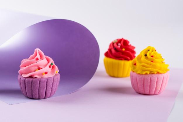 振りかけると明るい紫色の背景に装飾的な色とりどりの砂糖カップケーキ