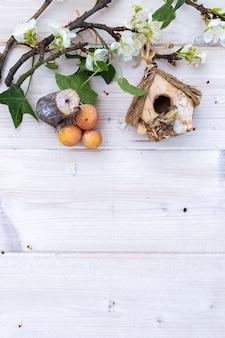 装飾的なキノコ、巣箱、テキスト用のスペースのある木製のテーブルに花が咲く枝