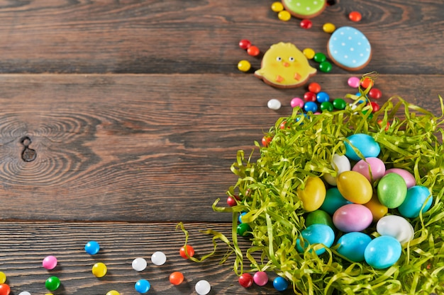 Decorative nest filled with easter eggs on wooden background