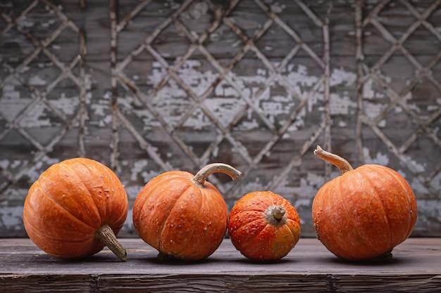 Декоративные оранжевые тыквы на темном деревянном столе. старый серый стол с геометрическим рисунком,