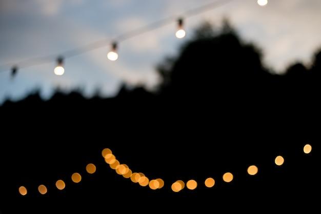 Декоративные наружные гирлянды в ночное время, расфокусированный фон, фон ночной городской жизни, время для вечеринок с желтыми шарами боке, лето