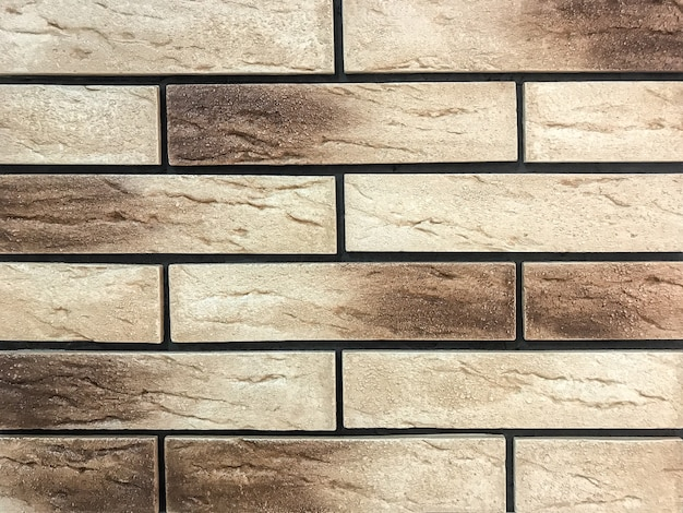 Decorative panel in the form of a beige and brown old brick.