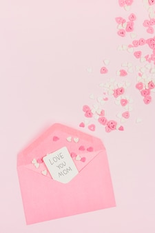 Decorative paper hearts near envelope with tag with words