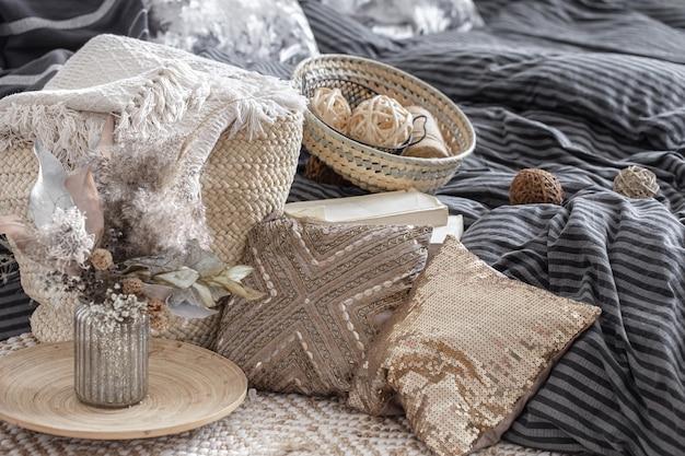 장식 베개, 말린 꽃이 달린 꽃병 및 파스텔 색상의 가정 장식의 다른 요소가 닫습니다.