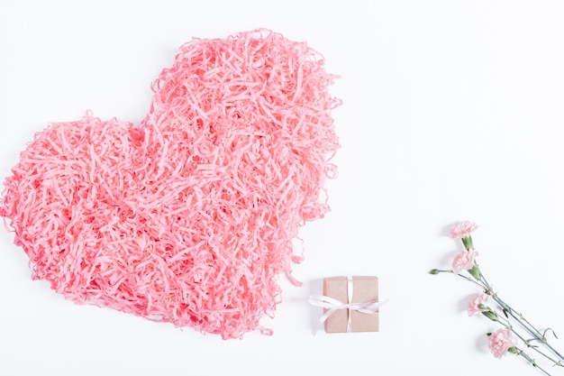 Decorative pink heart, small box with a gift and ribbon and flowers on a white surface
