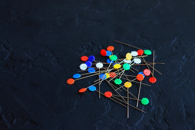 Decorative pins scattered on a dark background the concept of sewing and needlework
