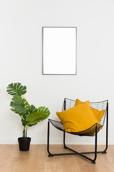 Decorative plant with empty frame and chair