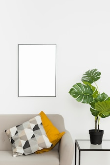 Decorative plant with empty frame and sofa
