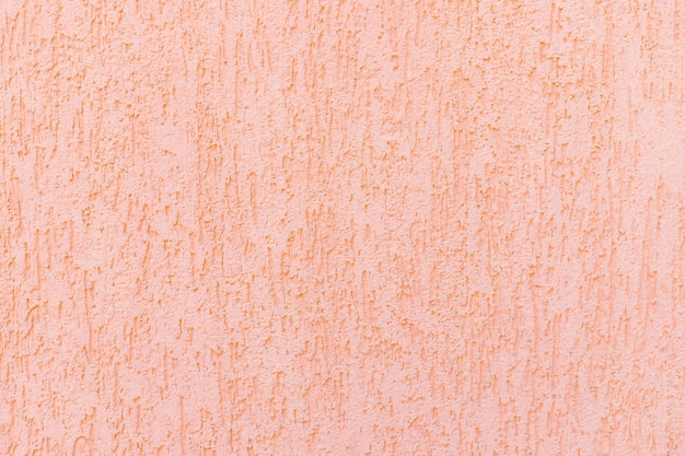 벽에 장식용 석고와 분홍색 페인트. 거칠고 고르지 않은 표면. 빈티지 배경 및 질감입니다.