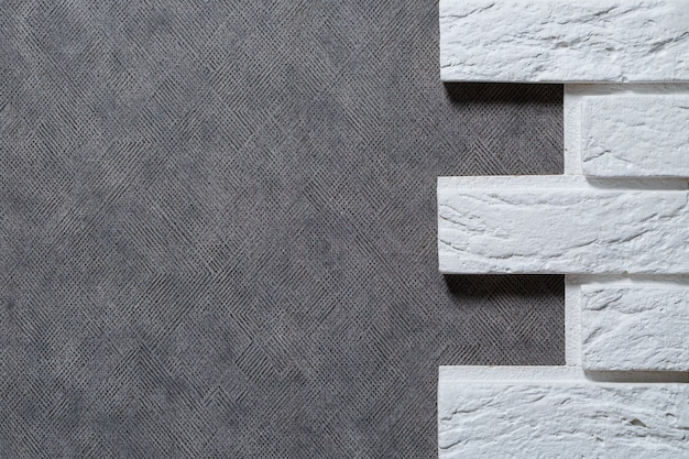 Decorative plaster brick. texture of light beige scratched embossed brick wall with white seams and rectangular stucco bricks.