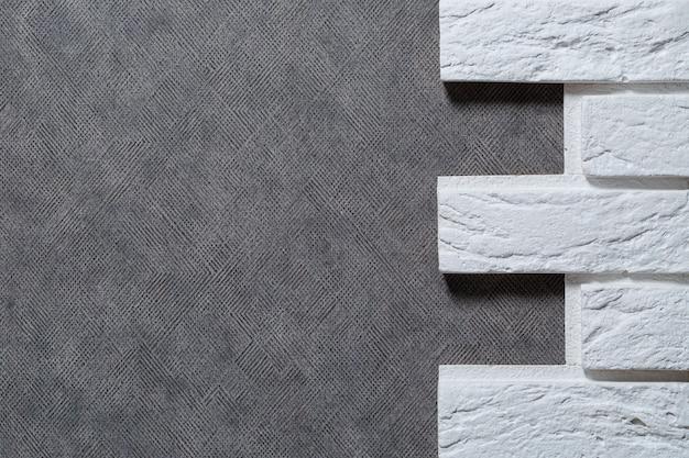장식용 석고 벽돌. 흰색 솔기와 직사각형 스투코 벽돌이 있는 밝은 베이지색 긁힌 양각 벽돌 벽의 질감.