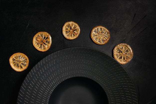 Decorative plate on black background decorated with dried citrus. unique art crockery. luxury style concept