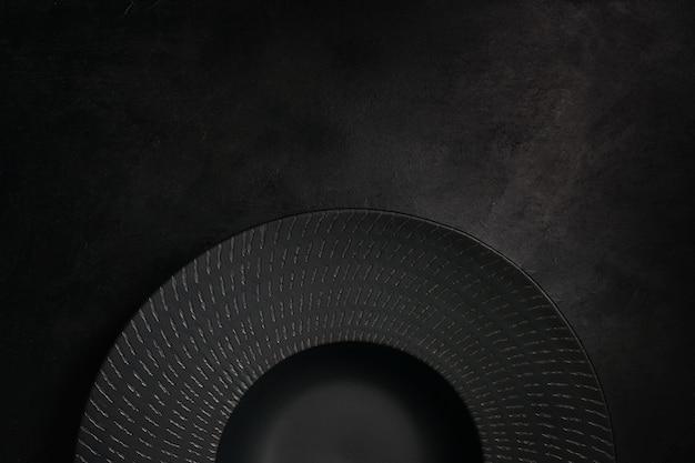 Decorative plate on black background. unique art crockery. luxury style concept