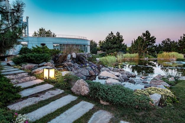 Декоративный пруд с искусственным водопадом во дворе загородного дома на летнем закате