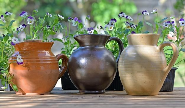 庭の花とテーブルの上に置かれた装飾的な陶器