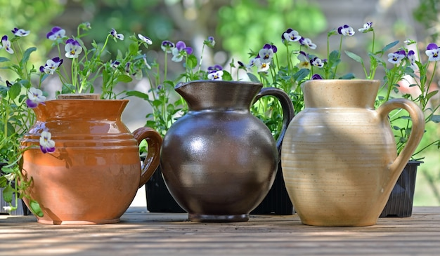 Decorative pottery  placed on a table with flowers  in garden