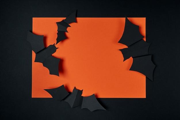 黒とオレンジ色の背景に装飾的なカボチャと紙コウモリ。ハロウィーンの休日のコンセプト。フラットレイアウト、フラットリー