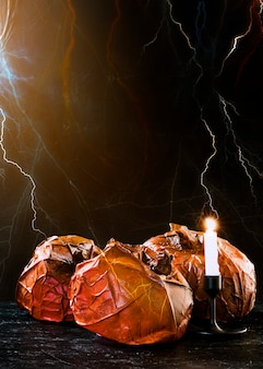 Decorative pumpkins and burning candle standing and lightning