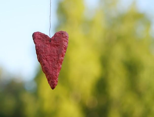 Декоративное красное сердце ручной работы на фоне природы.