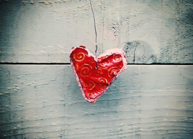 Декоративное красное сердце ручной работы на деревянных фоне.