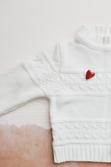 Decorative red heart on knitted sweater.