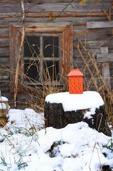 Декоративный красный фонарь с горящей свечой в сельской местности на открытом воздухе на фоне старой сельской бани.