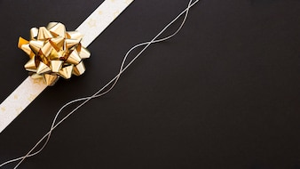 Decorative ribbon bow and silver string on black background