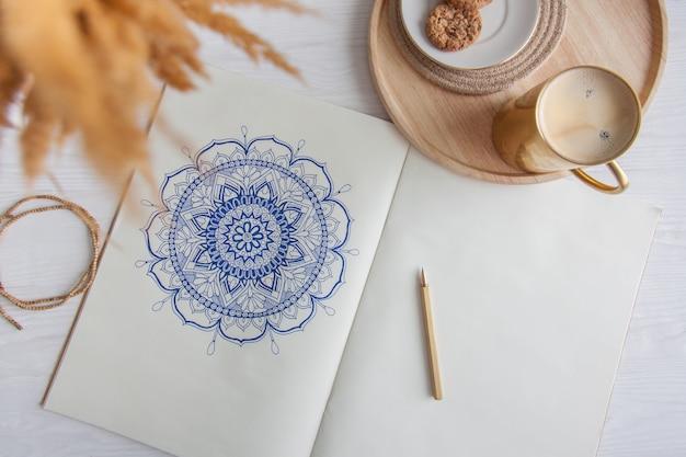 白いシートに描かれた装飾的な丸い花曼荼羅。ホームリラクゼーション、趣味、休息。コーヒーと白い背景の上のクッキー。