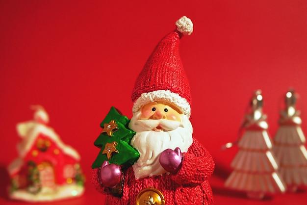 Декоративный санта-клаус с рождественской елкой против рождественского домика и серебряных деревьев.