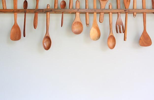 Декоративный набор деревянной кухонной утвари, висящей на белой стене